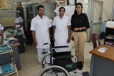 Personal från Projects Abroad och personal från National Cancer Institute står bredvid en rullstol som donerades till sjukhuset.