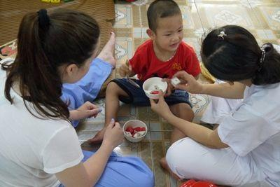 Occupational Therapy volunteer Amanda Chilkotowsky (USA) working with physically disabled child, and staff therapist, at Thuy An Rehabilitation Centre