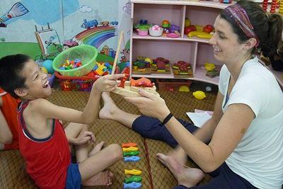 Occupational Therapy volunteer Jillian Meyers (USA) working with physically disabled child at Thuy An Rehabilitation Centre