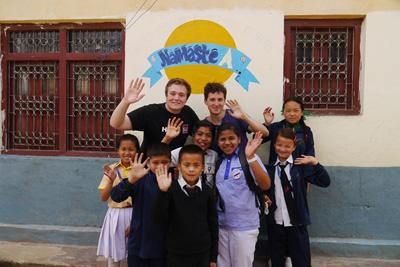 Malte and Harry wave with school children at Deepmala's English camp in Nepal, where they taught English, drama, sport, and craft activities