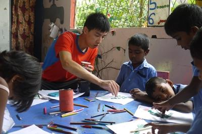 Projects Abroad Care volunteer, Herman Chi Hong Chan, does arts and crafts with children at his placement at Dutch Anne Preschool in Panadura.
