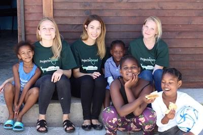 Projects Abroad Nutrition volunteers sit with a group of young girls at their placement in Cape Town, South Africa