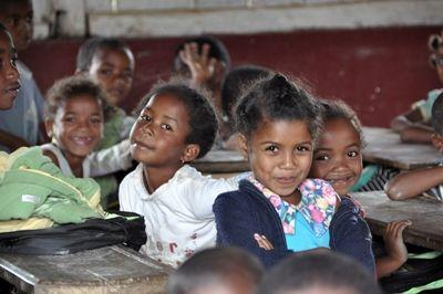 Happy children smile at a local school at a Projects Abroad Teaching placement in Madagascar