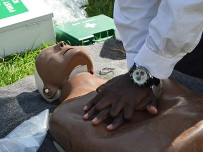 A Kenyan man who works at a Projects Abroad placement practices CPR during a first aid training demonstration in Nanyuki, Kenya