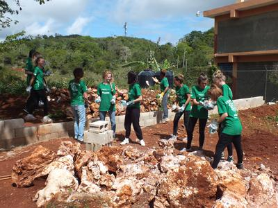 Volunteers clear stones to build a playground in Jamaica