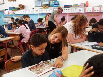 Teaching volunteers help a young class during reading time