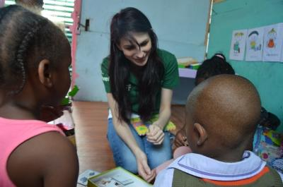 Children play with their new educational games with the help of a staff member