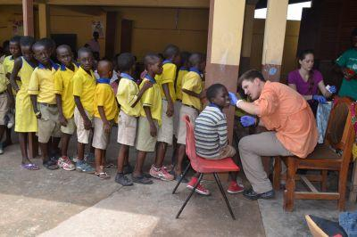 A Ghanaian school girl gets a health check from a volunteer.