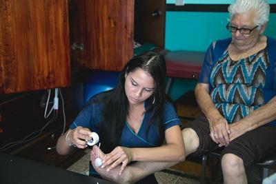 A senior receives electrode treatment from Projects Abroad intern for a foot problem at Asociacion Centro de Atención al Anciano Francisca Valerio Badilla