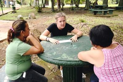 Projects Abroad Business volunteer, Anna Tapiolas-Verdera from Spain, discusses the appropriate way to manage a specific situation during a scenario exercise with members of the Asociacion Centro de Reciclaje de Belen