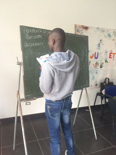 Refugee in Italy writes on a blackboard during his Italian class