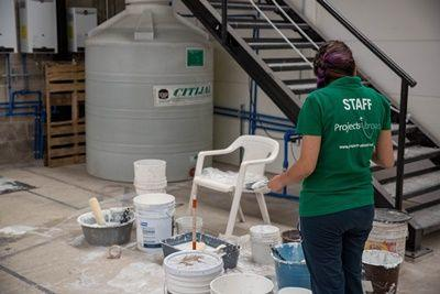Community day helper, Arely Maldonado begins work painting at FM4 Paso Libre