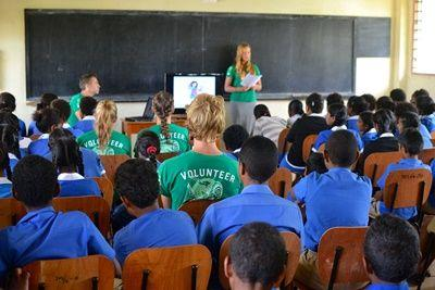 A female volunteer speaks to young Fijians during a shark education initiative