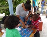 Freiwillige und Kinder spielen ein Brettspiel