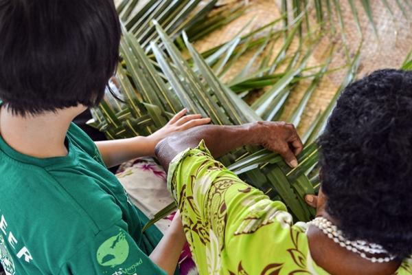 """Am """"community day"""" im Dorf lernen Freiwillige die traditionelle Herstellung von Matten"""