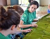 Freiwillige lernen das Knüpfen eines traditionellen Hüttendaches