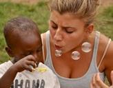 Eine Freiwilligen spielt mit einem Jungen mit Seifenblasen in Ghana