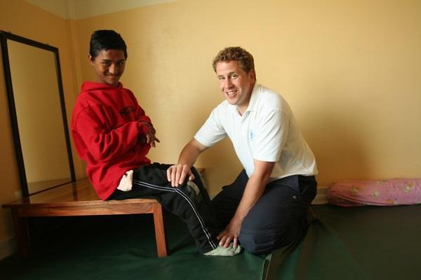 Freiwilliger macht Physiotherapie-Übungen mit einem Jungen