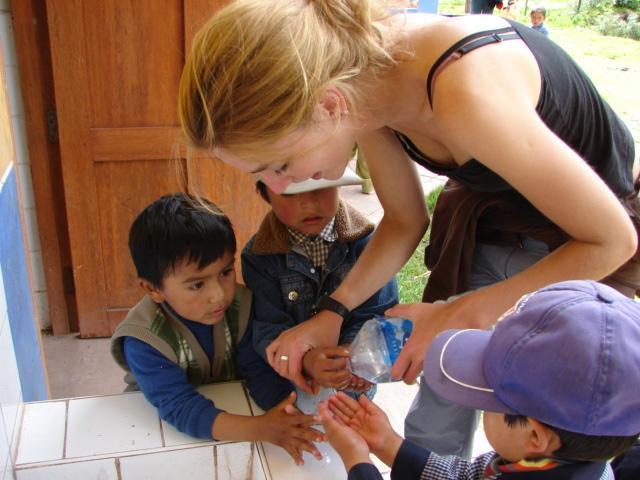 Frivillig hjælper børn med at vaske hænder i Peru