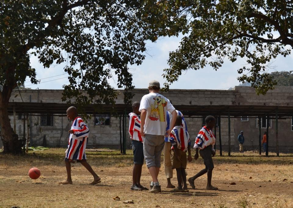 Frivillig spiller fodbold med børnene efter skoletid