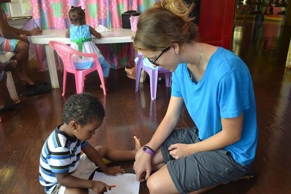 Un volontaire enseigne l'alphabet  à un enfant