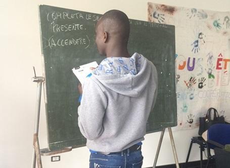 Des réfugiés dans une salle de classe en Italie où les volontaires leurs donnent des cours d'anglais.