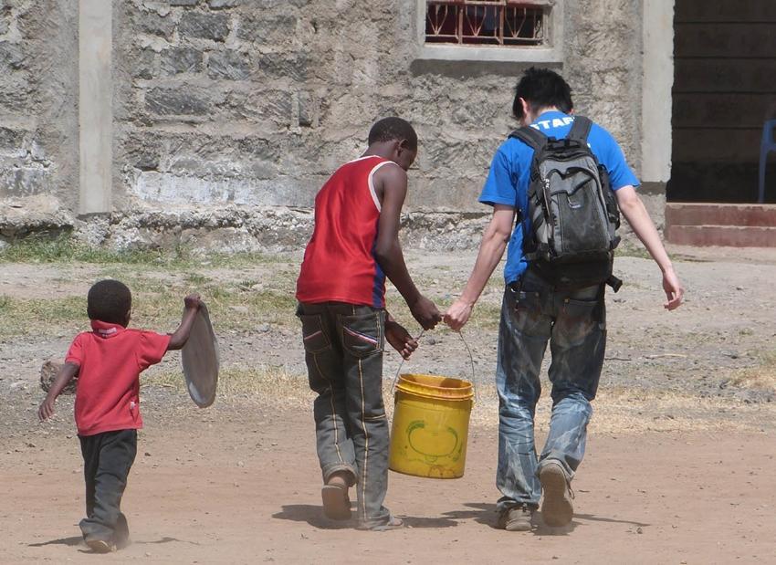 Un volontaire porte un sceau d'eau au Kenya