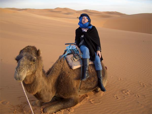 Découverte culturelle, une volontaire sur un chameau dans le Sahara au Maroc