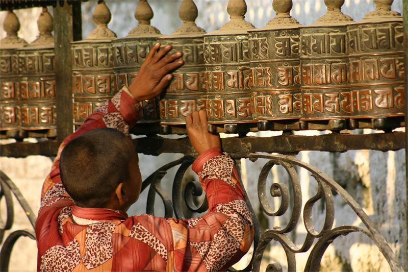 Enfant près d'une roue à prières au Népal