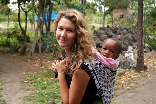 Volontaire porte un bébé sur son dos en Tanzanie