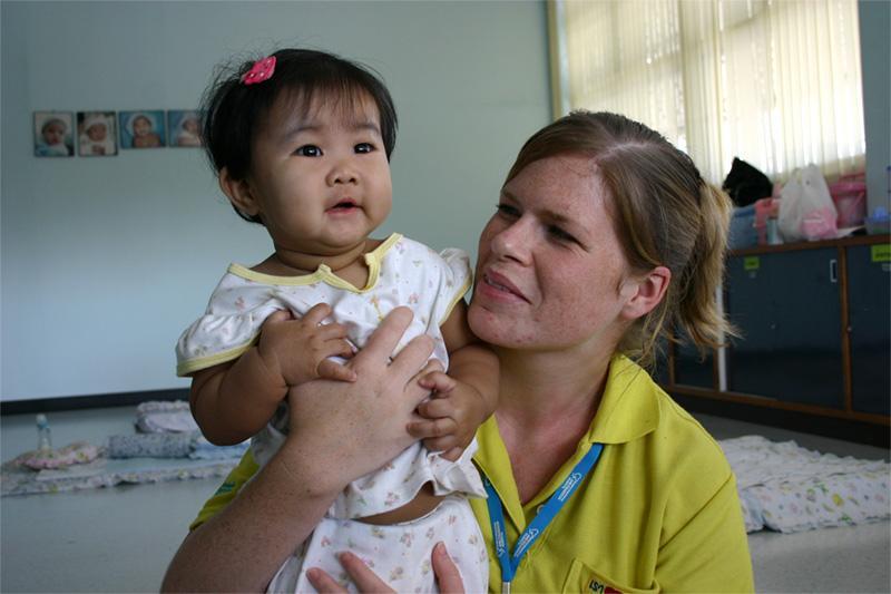 Volontaire avec un bébé sur une mission humanitaire en Thaïlande