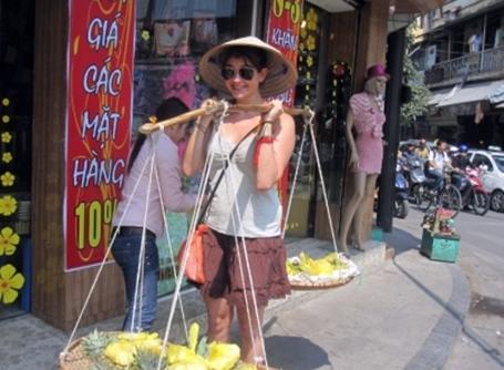 Découverte culturelle, une volontaire porte des fruits à la façon locale au Vietnam