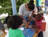 Volunteer plays board games at a Care project in Belize