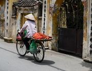 Una donna vietnamita pedala nei pressi di un tempio cinese