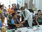 La volontaria italiana aiuta un bambino durante una campagna di sensibilizzazione in Vietnam