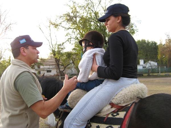 アルゼンチンの乗馬セラピープロジェクトで子供を馬に乗せるボランティア