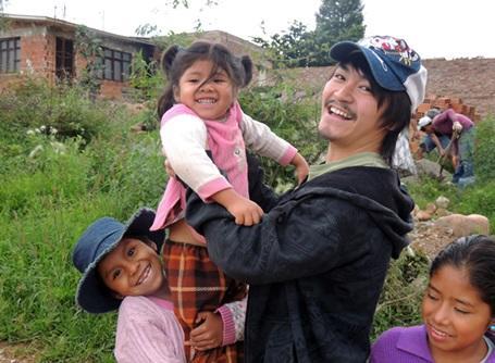 ボリビアで現地の子供を抱き上げるプロジェクトアブロードのボランティア