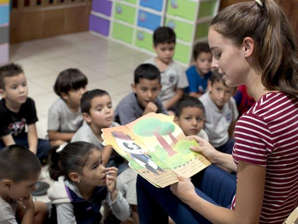 コスタリカのケアプロジェクトで子供たちに本を読み聞かせるボランティア
