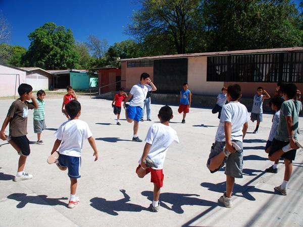 コスタリカのスポーツプロジェクトで子供たちとストレッチを行うボランティア