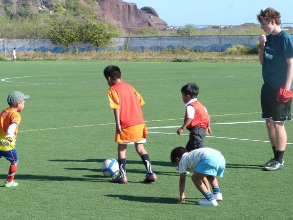エクアドルのガラパゴス諸島で行われているスポーツプロジェクトで子供たちにサッカーを教えるボランティア