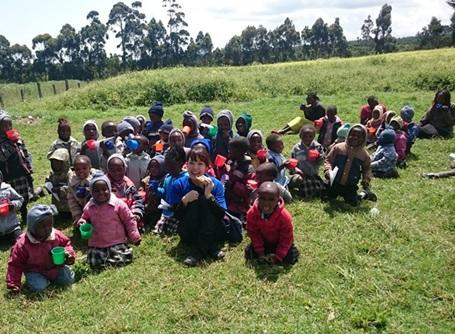 ケニアのケアセンターで子供たちと昼ご飯を食べるケアボランティア
