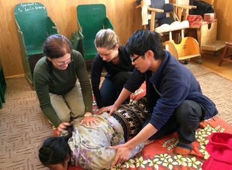 ネパールのケア施設で行われている理学療法プロジェクトでリハビリを行うボランティア