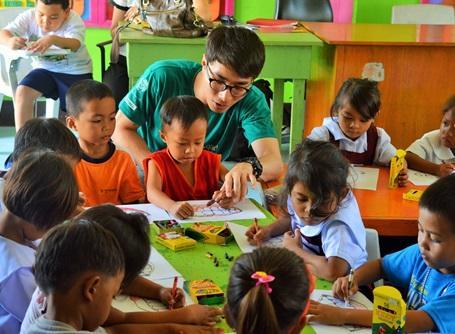 ケアプロジェクトで子供たちと絵を描くプロジェクトアブロードのボランティア