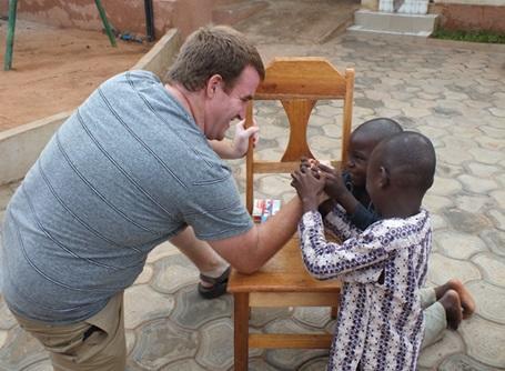 ケアプロジェクトで子供と腕相撲をするプロジェクトアブロードのボランティア