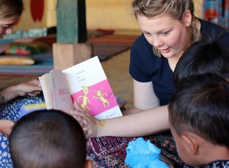 프로젝트어브로드 캄보디아의 데이케어 센터에서 아이들과 책을 읽고 있는 어린 봉사자