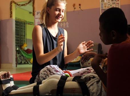 캄보디아의 물리치료 봉사자가 활동지의 소년과 함께 일하고 있다