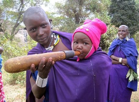 탄자니아 현지 마을에서 아기에게 밥을 먹이는 마사이족 여성