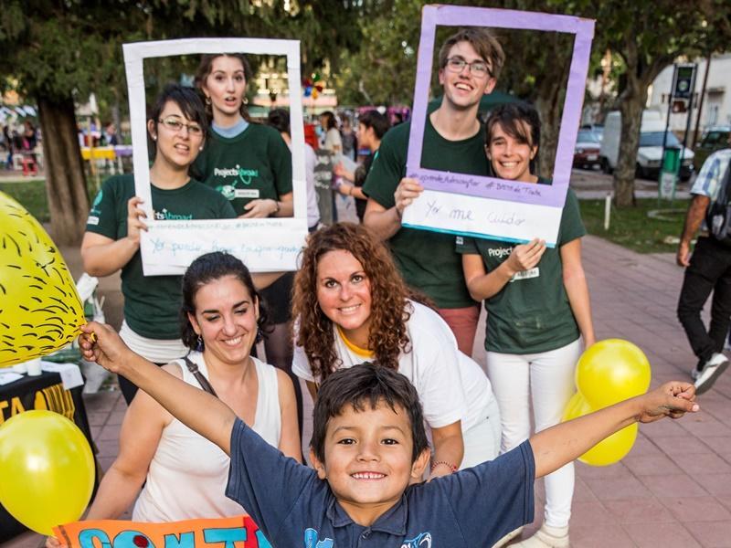 Een Argentijnse jongetje springt voor de foto van vrijwilligers van het Mensenrechten project