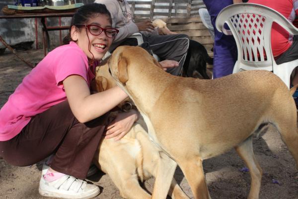 Een meisje in een opvangcentrum speelt met de honden van het hondentherapie project in Cordoba, Argentinië