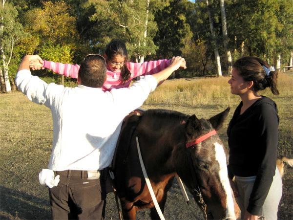 Projects Abroad vrijwilliger helpt een meisje bij het paardenproject in Argentinië